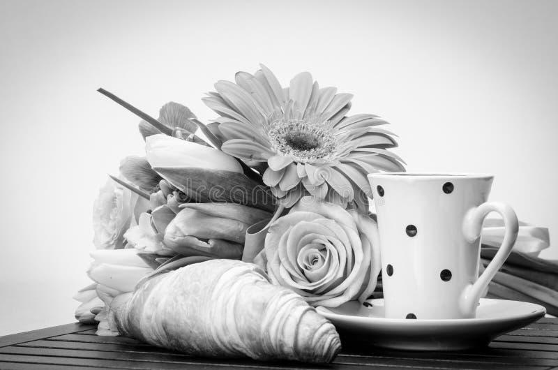 Cruasán, taza con el platillo y flores imagen de archivo libre de regalías