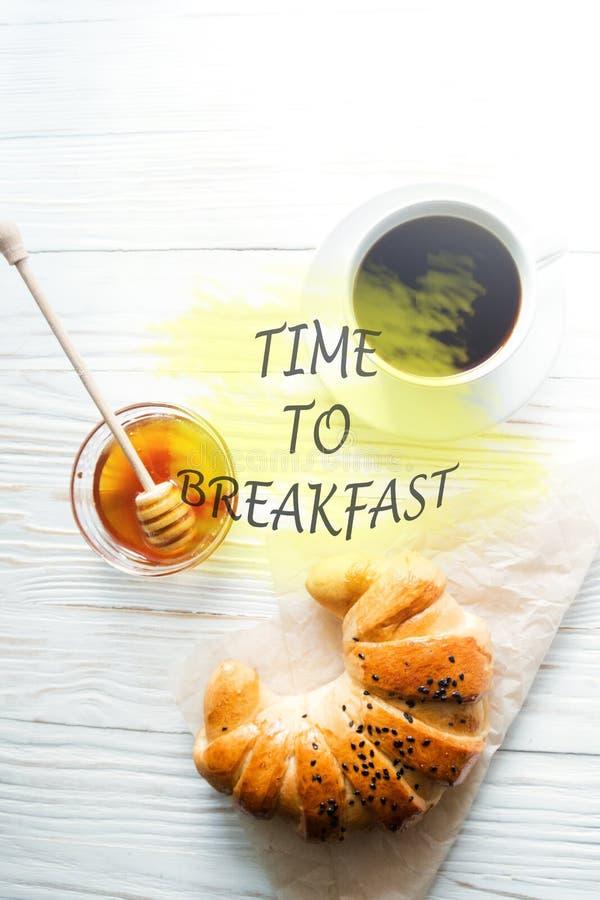 Cruasán, una taza de café instantáneo y miel en un fondo de madera texturizado blanco con la época de la inscripción de desayunar foto de archivo
