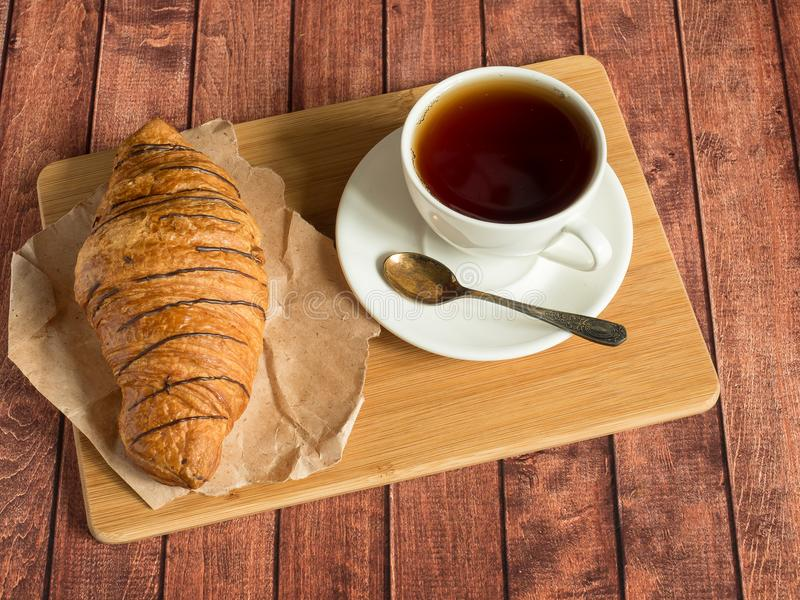 Cruasán y té del desayuno en una servilleta de la materia textil Fondo de madera oscuro fotos de archivo libres de regalías