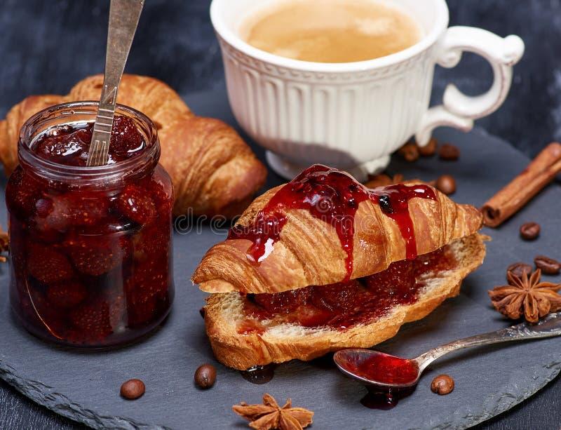 Cruas?n con la mermelada de fresa y la taza blanca con caf? fotografía de archivo