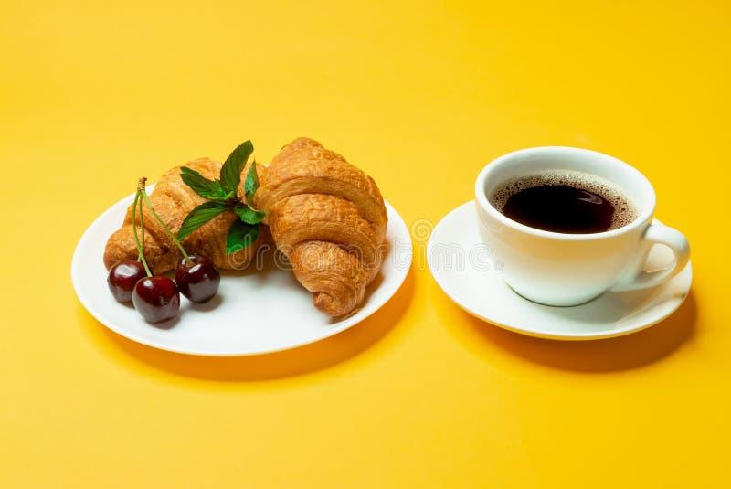 Cruasanes, café, cerezas en fondo amarillo fotografía de archivo