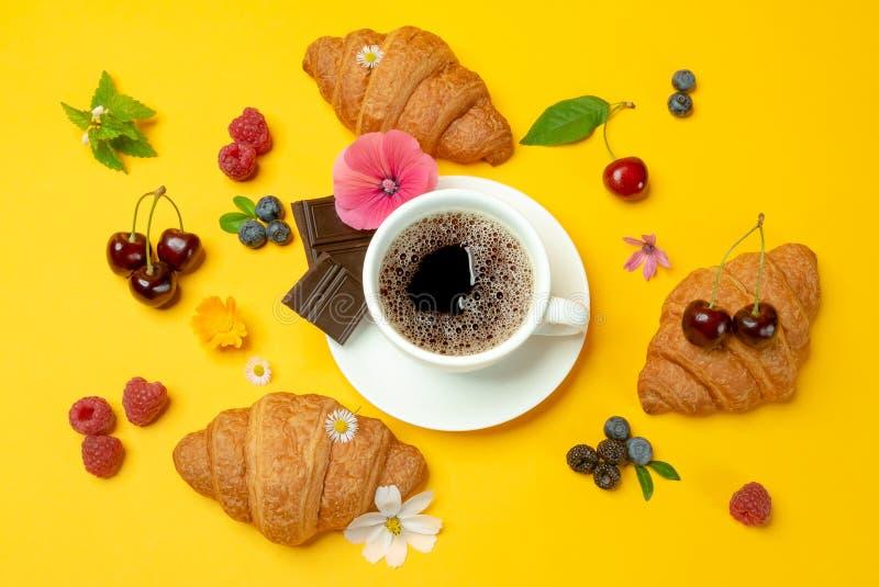 Cruasanes, coffe, flores y bayas en fondo amarillo foto de archivo libre de regalías