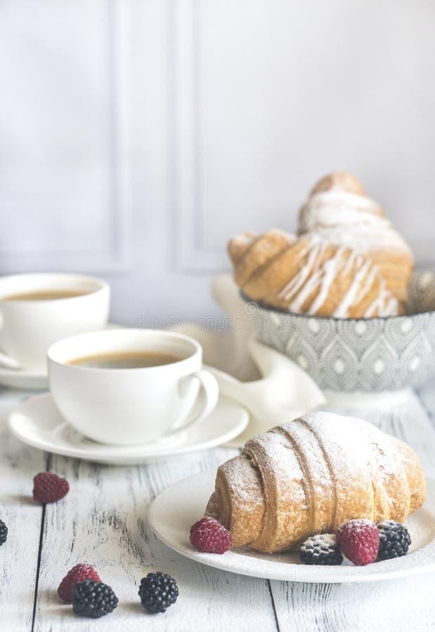 Cruasanes con las bayas frescas y dos tazas de café fotos de archivo