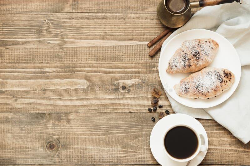 Cruasanes del chocolate y taza recientemente cocidos de café sólo en tabla de cortar de madera Visión superior Concepto del desay fotografía de archivo libre de regalías