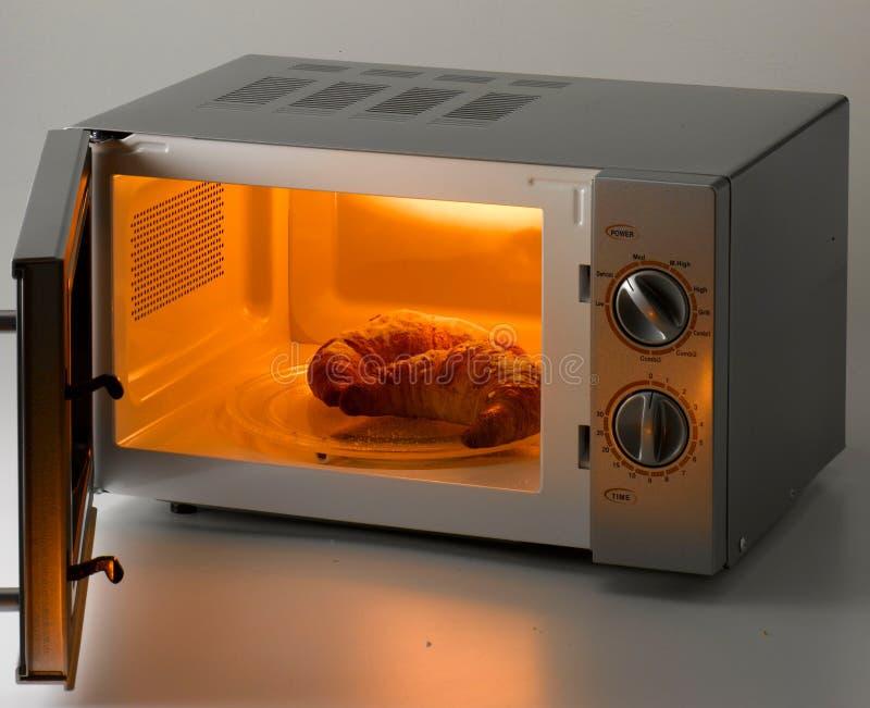 Cruasanes en un horno de microondas abierto foto de archivo