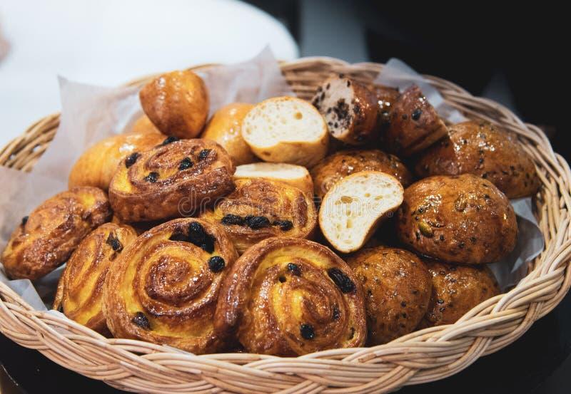 Cruasanes franceses en la cesta de mimbre, fondo de la panadería imagenes de archivo