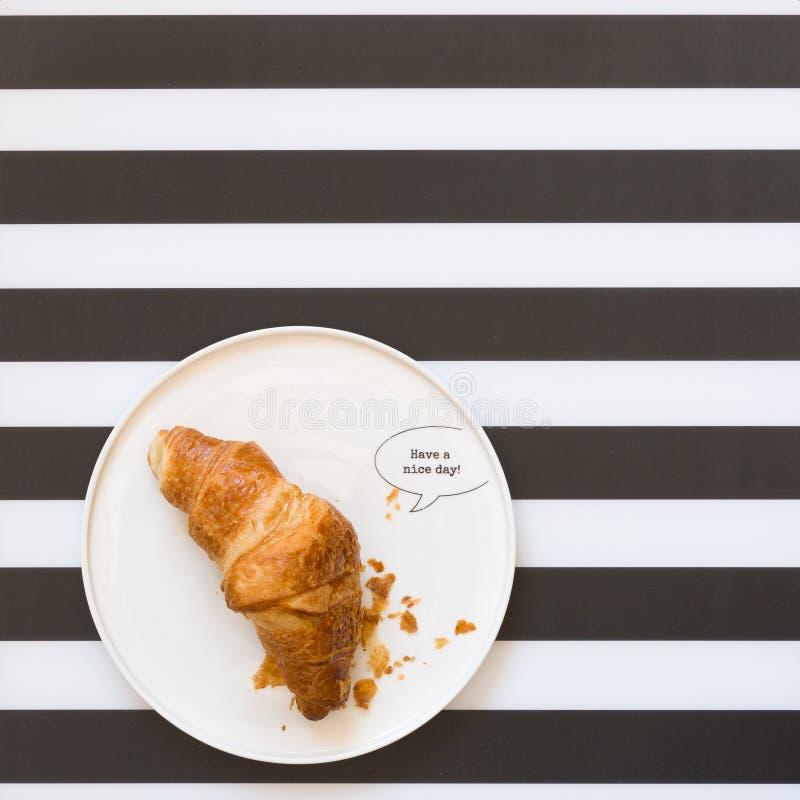 Cruasanes franceses en una placa en el fondo rayado, visión superior El desayuno delicioso tiene un día agradable fotografía de archivo