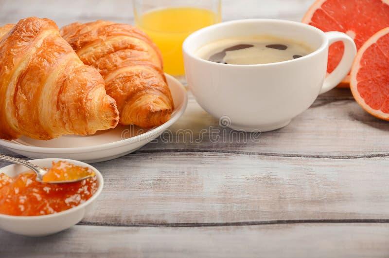 Cruasanes frescos con café, atasco y zumo de naranja para el desayuno en fondo de madera rústico fotografía de archivo libre de regalías