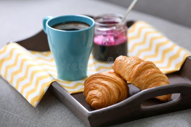 Cruasanes frescos, taza de café y tarro con el atasco imagenes de archivo