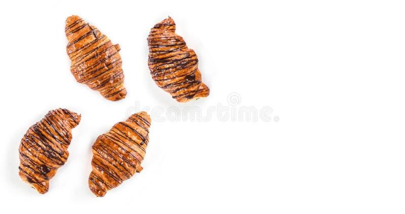 Cruasanes recientemente cocidos adornados con la salsa de chocolate aislada en el fondo blanco, visión superior fotografía de archivo