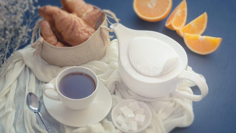 Cruasanes recientemente cocidos en la cesta y la taza de té en una oscuridad fotografía de archivo