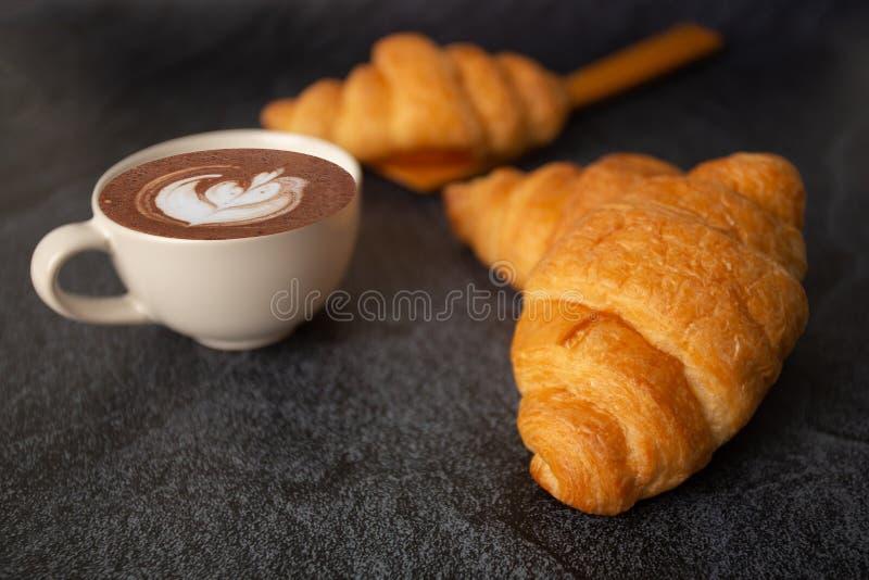 Cruasanes recientemente cocidos en un fondo negro con una taza del café con leche, mañana de la bebida del marrón del pan del des fotografía de archivo