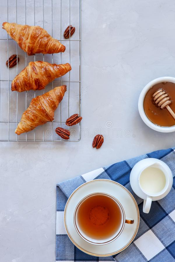 Cruasanes sabrosos frescos, taza de té, leche, miel foto de archivo libre de regalías