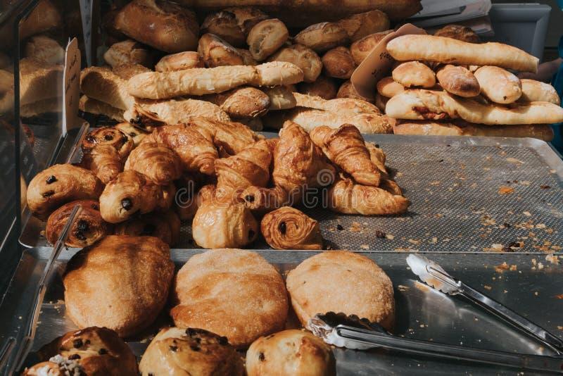 Cruasanes y panes fragantes frescos en la tabla , Variedad de productos cocidos en la tienda del pan imagenes de archivo