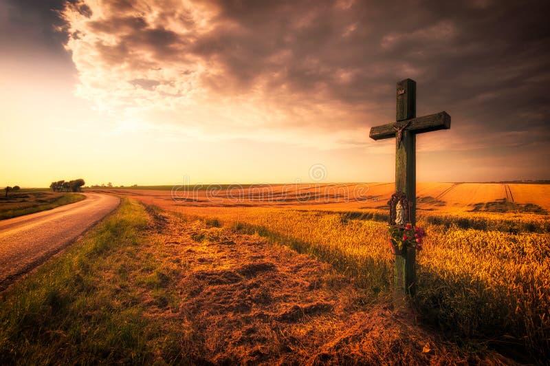 Cruce encima el campo durante puesta del sol fotos de archivo libres de regalías