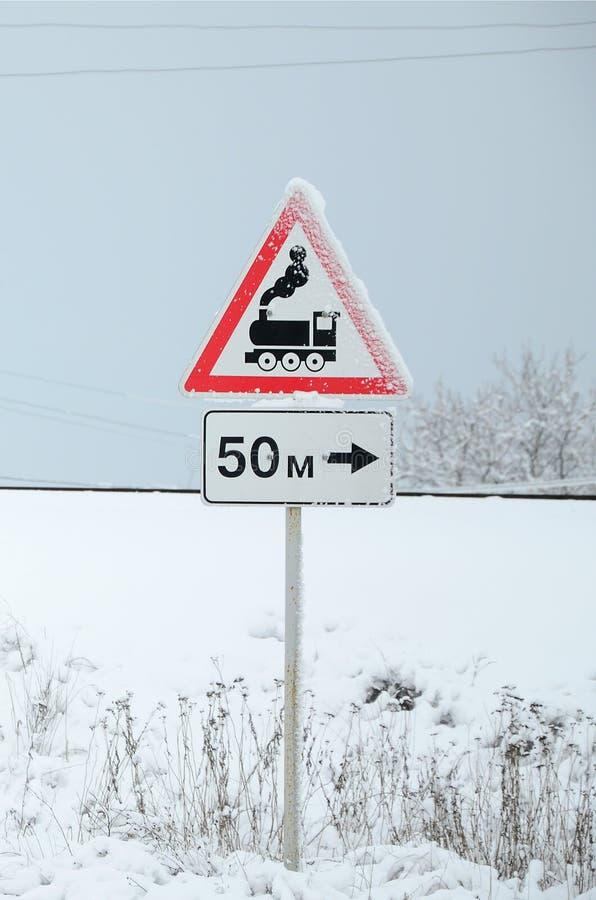 Cruce ferroviario sin barrera Una señal de tráfico que representa una locomotora negra vieja, situada en un triángulo rojo fotografía de archivo