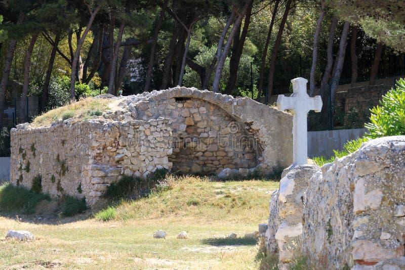 Cruce y las ruinas cerca del La Couronnede Chapelle de Sainte Croix à fotos de archivo libres de regalías