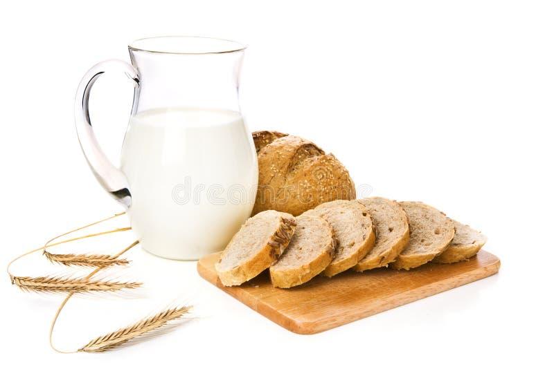 Cruche avec du lait, le pain et le blé images stock