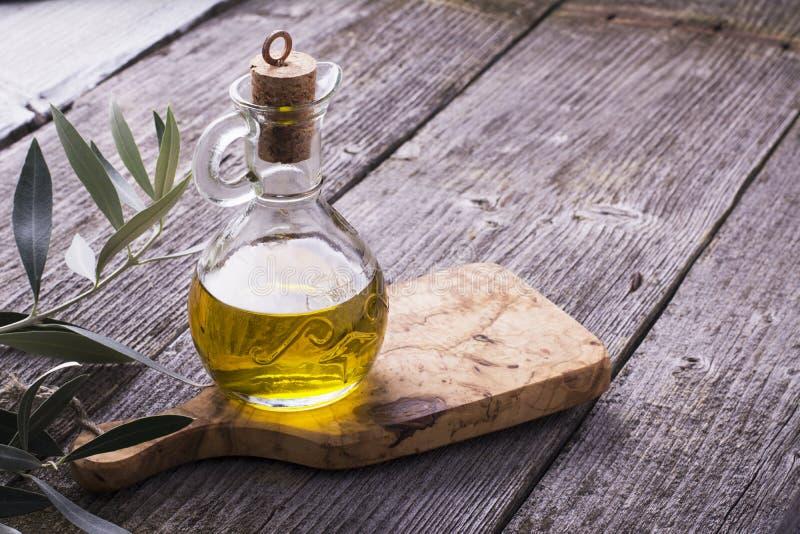 Cruche avec l'huile d'olive vierge supplémentaire sur la planche à découper entourée par des branches photographie stock libre de droits