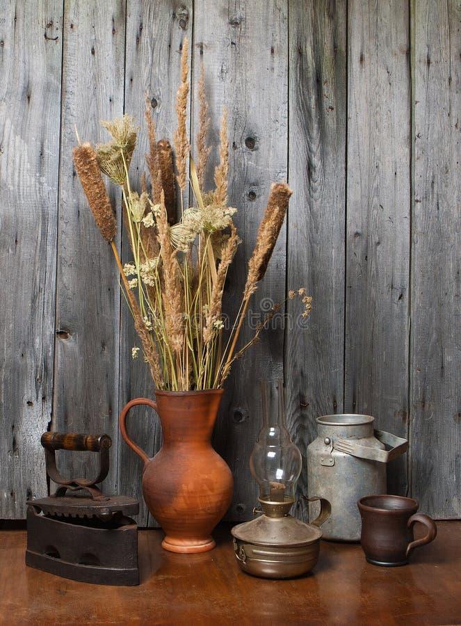 Cruche avec les roseaux secs et les vieilles choses photo stock