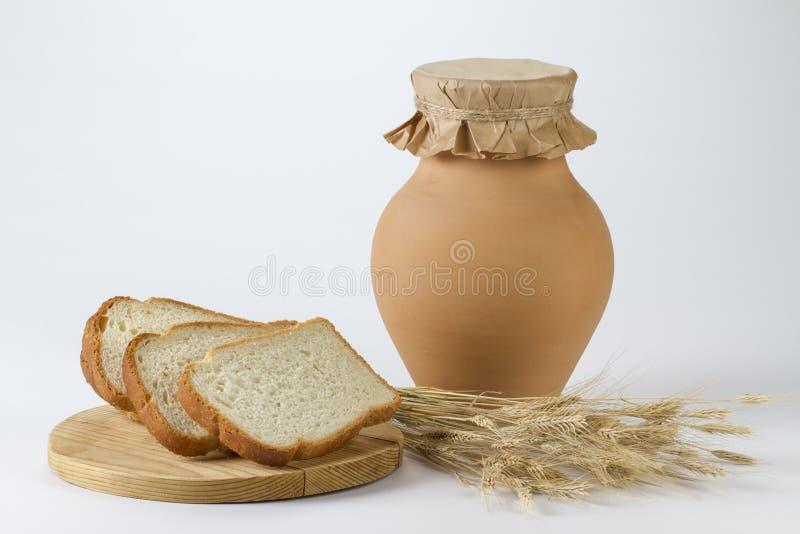 Cruche de lait avec les oreilles fraîchement cuites au four de pain blanc et de blé photo libre de droits