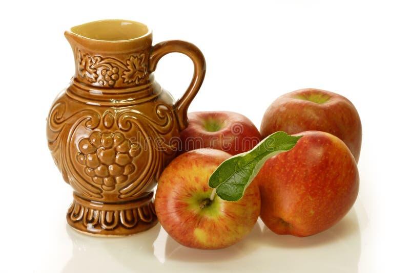 Cruche de vin de Brown avec des pommes photo libre de droits