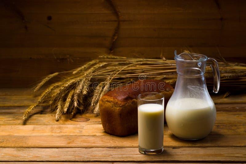 Cruche en verre avec du lait, tasse avec du lait, un pain de pain de seigle, oreilles photos stock