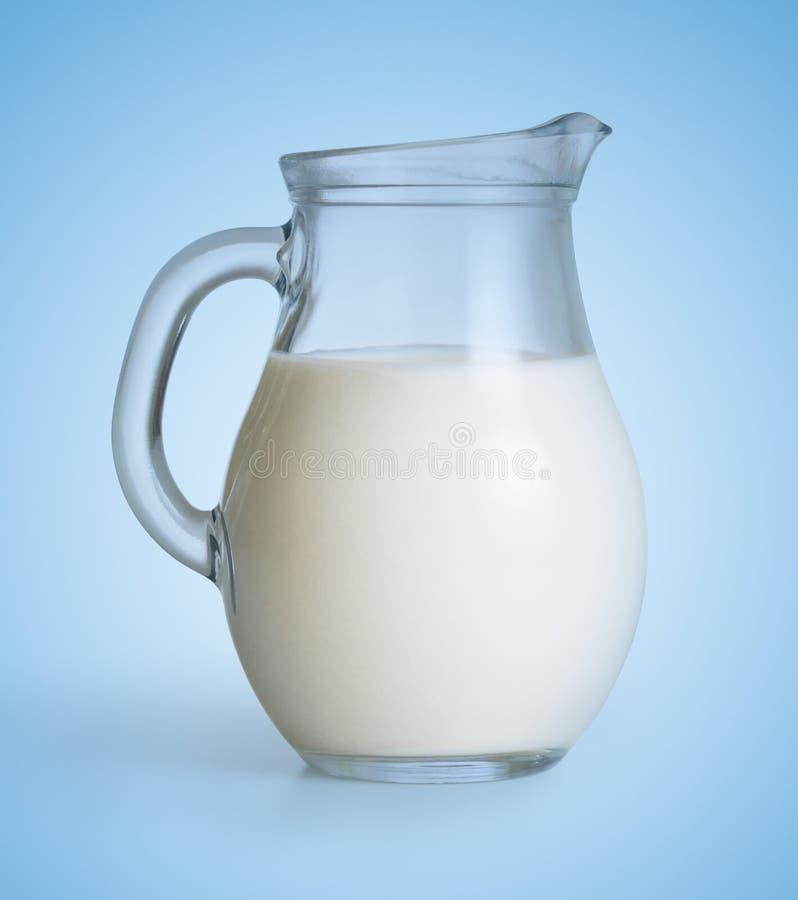 Cruche en verre de lait sur le bleu photo libre de droits