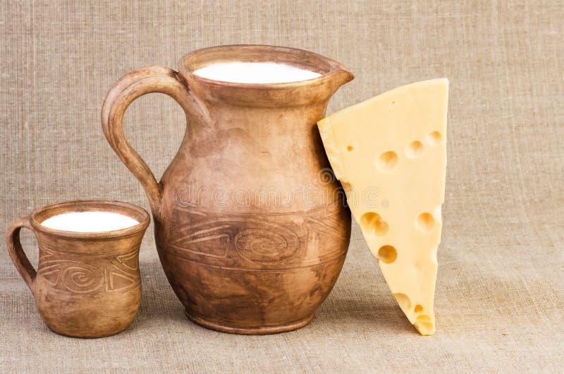 Cruche et tasse d'argile, et morceau de fromage photos libres de droits