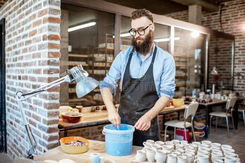 Cruches de peinture d'argile de travailleur au magasin de poterie photographie stock libre de droits