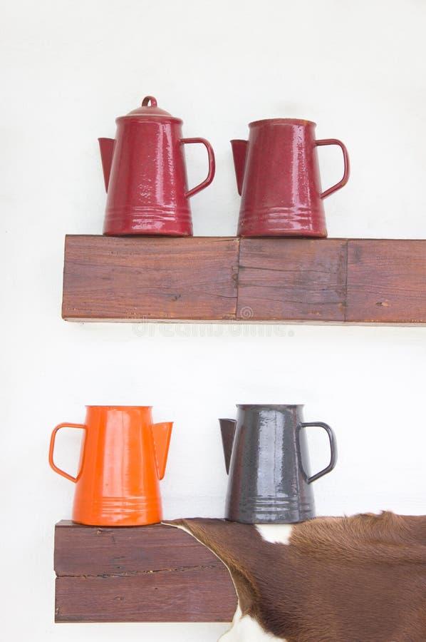 Cruches en métal sur l'étagère en bois. image stock
