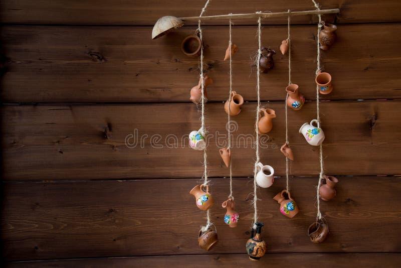 Cruches miniatures d'argile pendant d'une corde sur le mur en bois image libre de droits