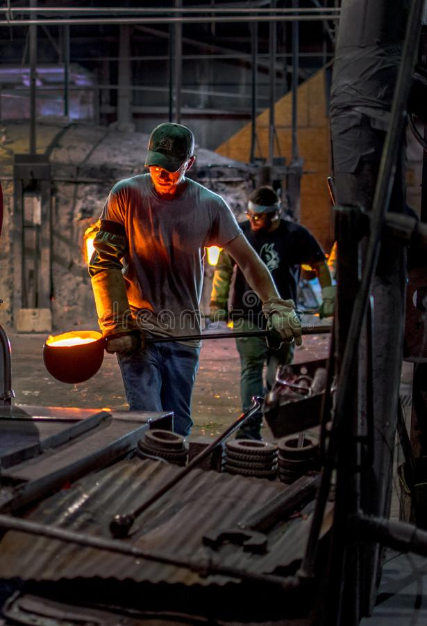 Crucible ladles of melted glass are carried by workers. Sept 27 2019 Kokomo Indiana USA; crucible ladles of molten glass are carried by workers to another royalty free stock photo