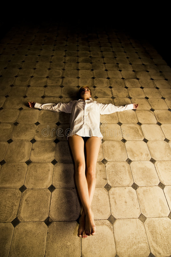 Crucified woman. Young seminude crucified woman on the floor royalty free stock photo