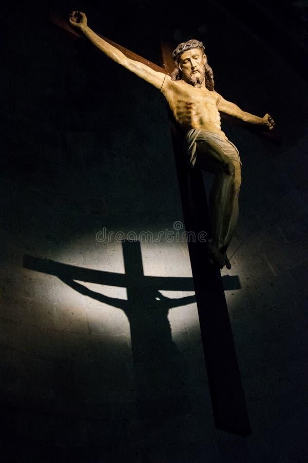 Crucifijo de madera antiguo iluminado dentro de una iglesia italiana hist?rica con la sombra echada en la pared imagen de archivo