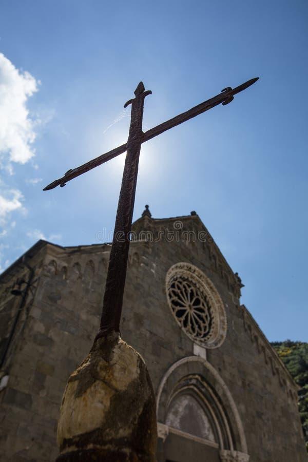 Crucifijo fuera de la iglesia en el cuadrado de la cumbre de Manarola, uno de los cinco pueblos de Cinque Terre - Manarola, La Sp fotos de archivo libres de regalías