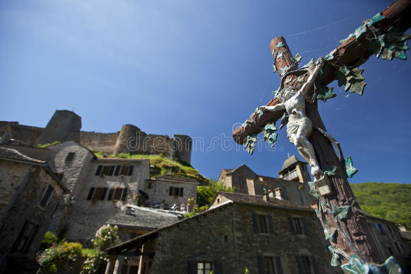 Crucifix. A roadside crucifix in the french village of Brousse-le-chateau, with its castle in the background stock images