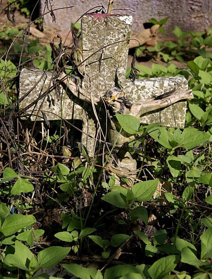 Crucifix of abandoned tomb among weeds. Stone crucifix of abandoned tomb in the cemetery of Xalapa Veracruz, Mexico 2017 stock photo