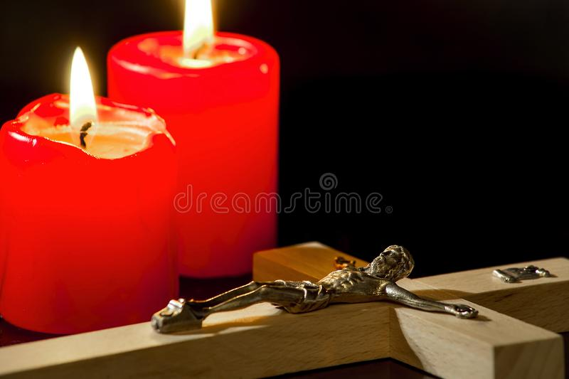 A crucifix against a background of lighted candles. On a black background royalty free stock images