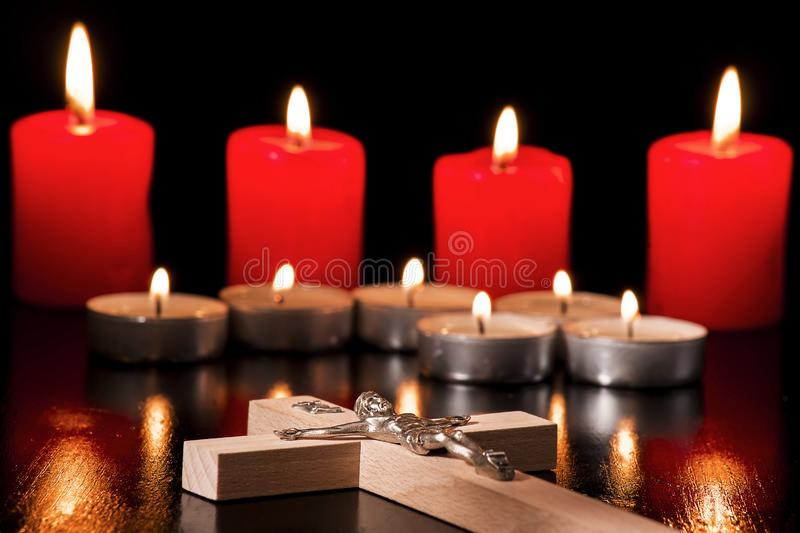 A crucifix against a background of lighted candles. On a black background royalty free stock photography