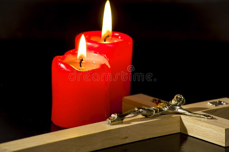 A crucifix against a background of lighted candles. On a black background royalty free stock photo