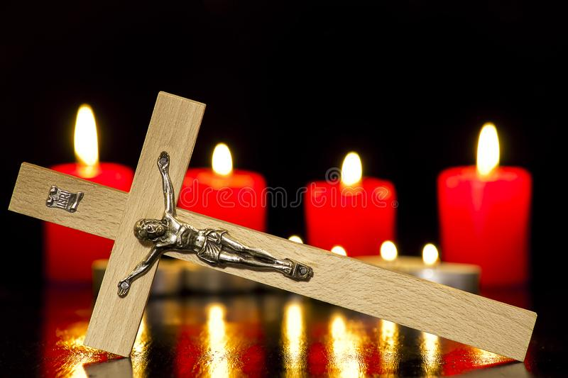 A crucifix against a background of lighted candles. On a black background stock photo