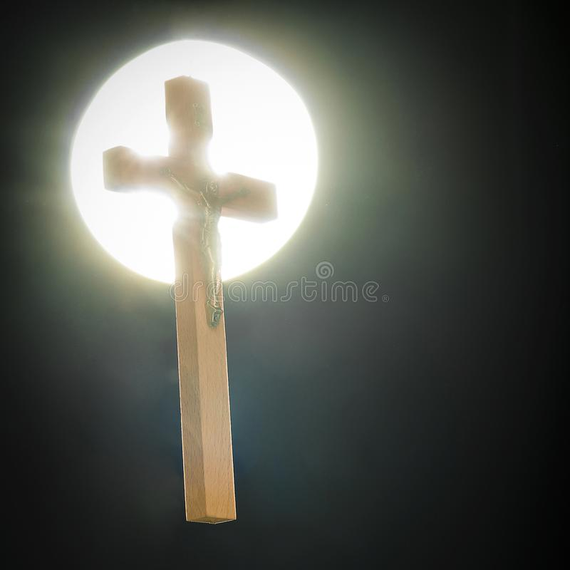 A crucifix against a round white light. Against a black background royalty free stock photos