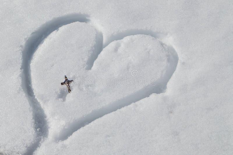Crucifix argenté sur le coeur dessiné dans la neige photographie stock libre de droits