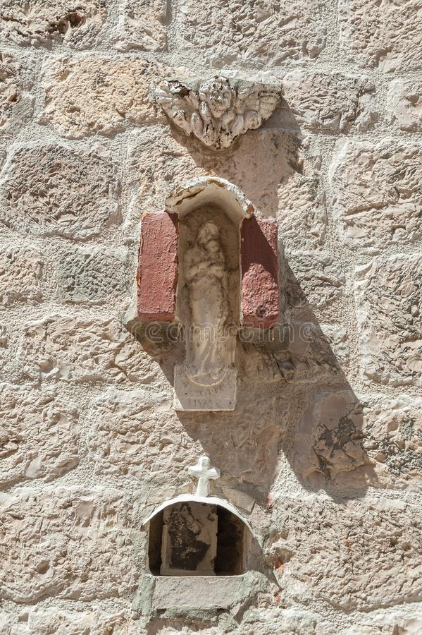 Crucifix. Art sculpture with photograph of Virgin Mary with Child. Hvar, Croatia. A sculpture of crucifix carved into stone in old masonry building. Below in royalty free stock images