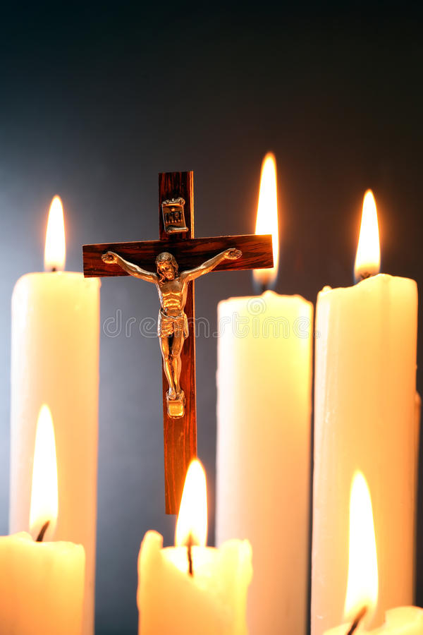 Crucifix And Candles. Small crucifix hanging on gray background among lighting candle royalty free stock photography