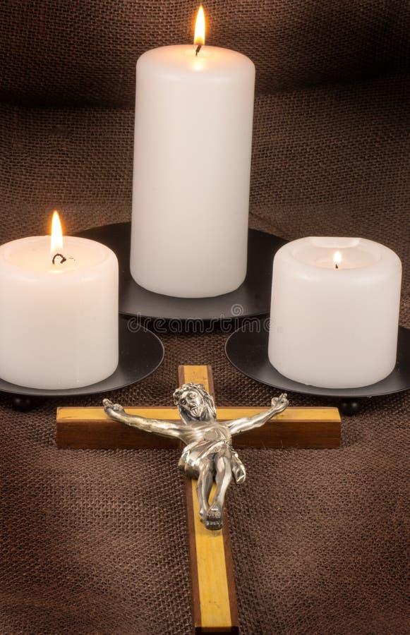 Crucifix et trois bougies photographie stock