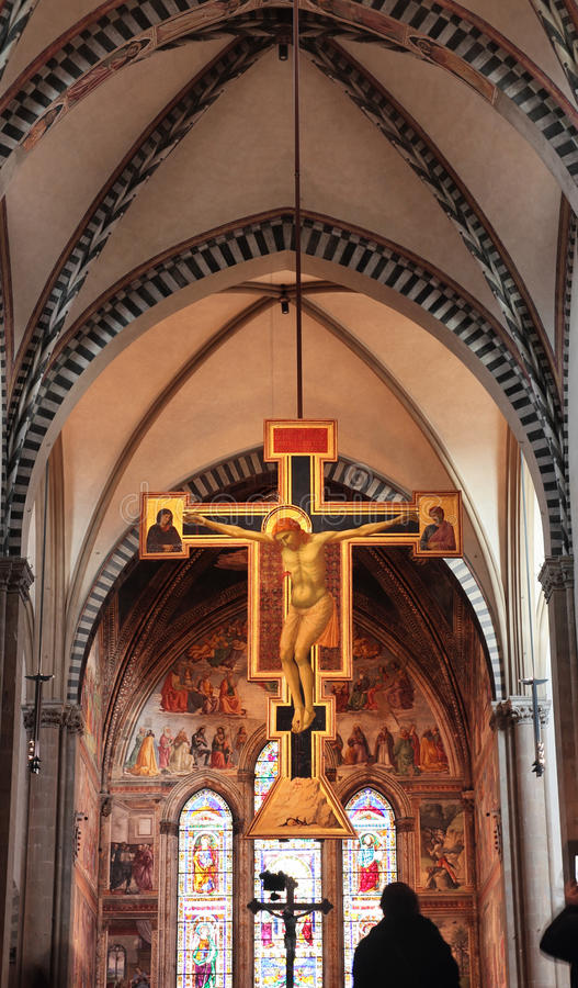 Crucifix by Giotto in Florence. FLORENCE, ITALY - DECEMBER 7, 2014:the central nave in Santa maria Novella Church with magnificent crucifix by Giotto, painted stock image