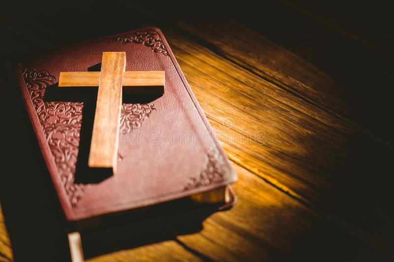 Crucifix icon resting on the bible. On wooden table stock photography