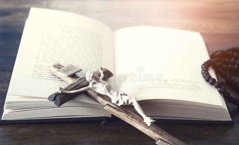 Crucifix with Jesus Christ and holy bible book stock image